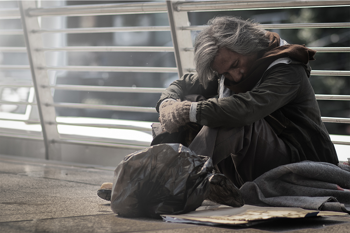 Obdachloser Mann mittleren Alters sitzt in Shoppingcenter