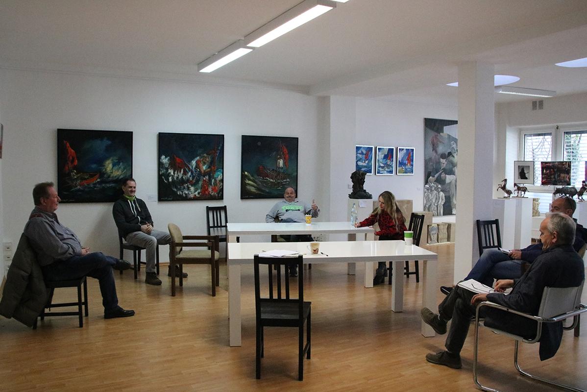 6 Menschen sitzen in einer Kunstgalerie im 1,5-Meter-Abstand bei einer Besprechung