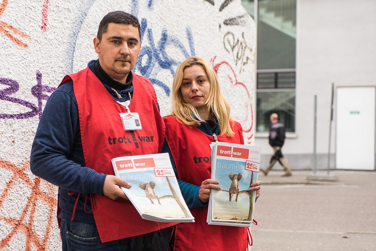 dunkelhaariger junger Mann und blonde junge Frau im Trott-war-Kittel und mit Zeitung in der Hand