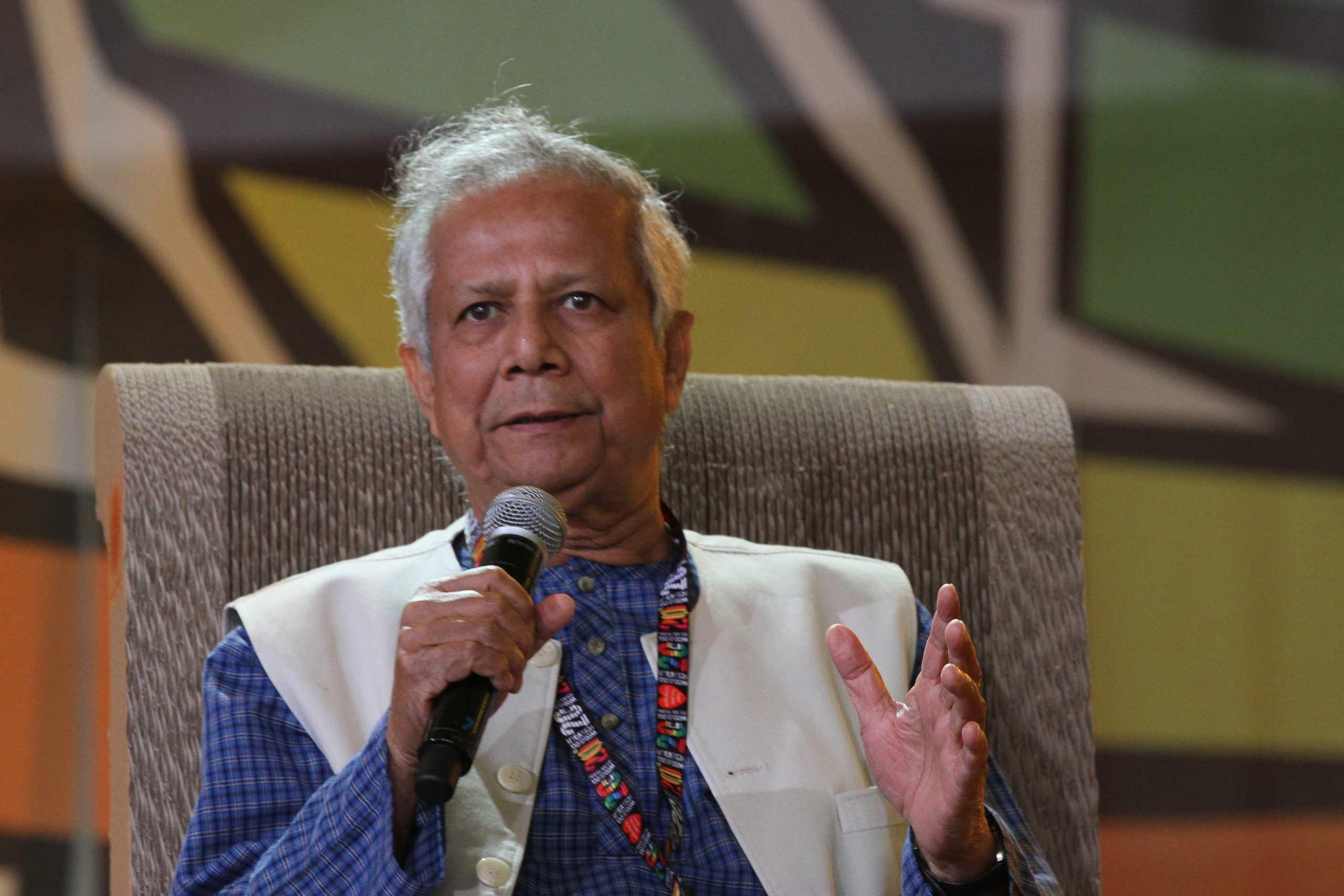 Der Interviewte, Muhammad Yunus, sitzt auf einem Stuhl und spricht in ein Mikrofon