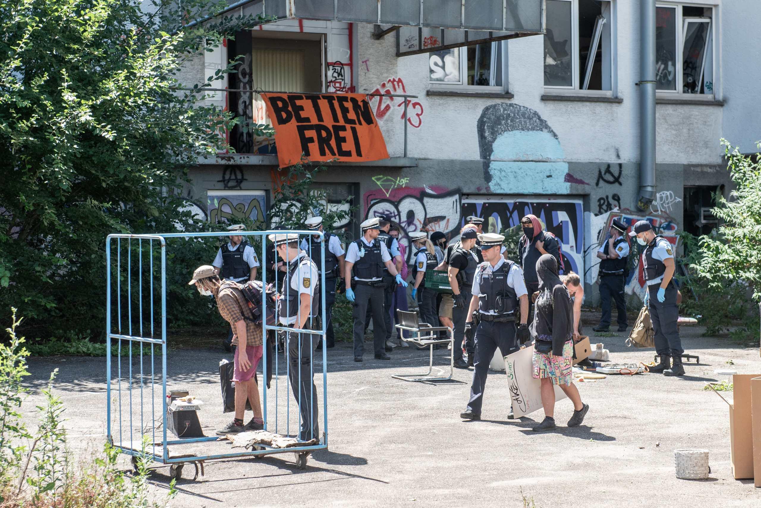 Die Besetzer im Hof des besetzten Gebäudes werden von der Polizei kontrollier