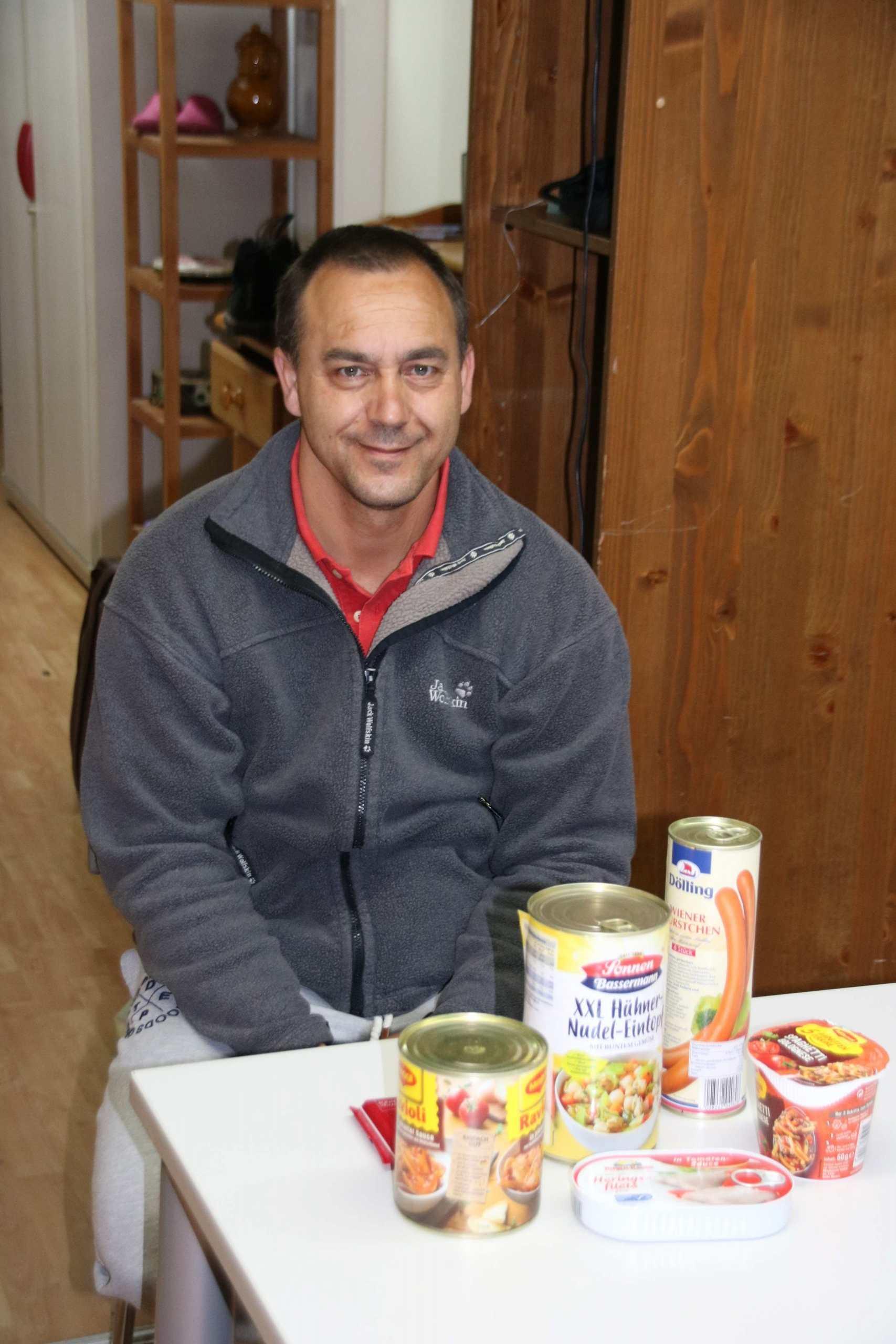 Trott-war-Verkäufer sitzt an Tisch mit den von der Spende gekauften Konserven