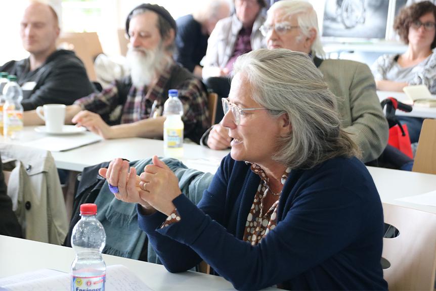 Eine Teilnehmerin aus dem Publikum spricht im Vordergrund, dahinter weitere Reihen von Teilnehmenden