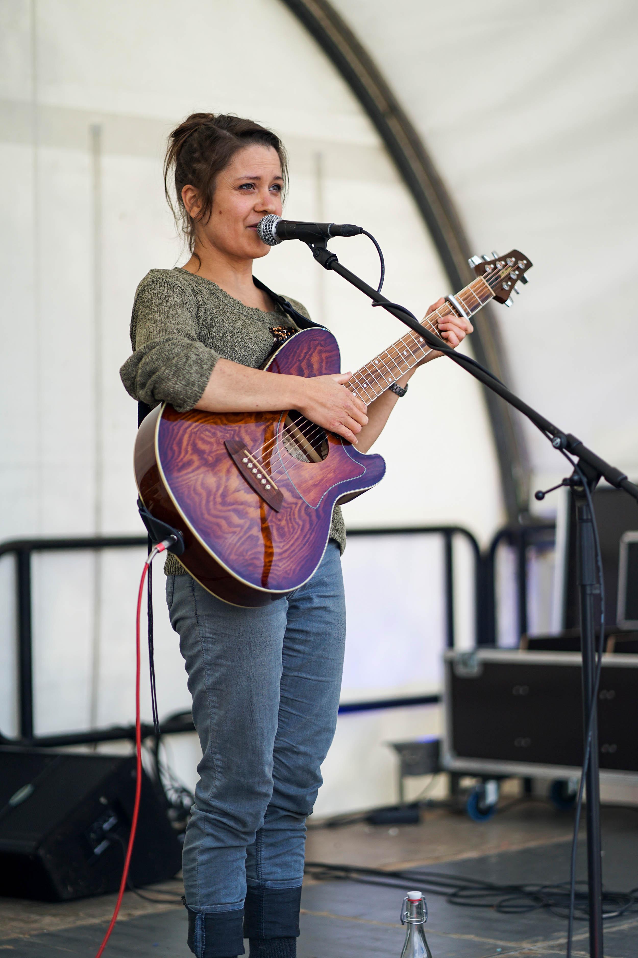 junge Frau zurückgesteckten brauen Haaren, Pulli, Jeans und Gitarre
