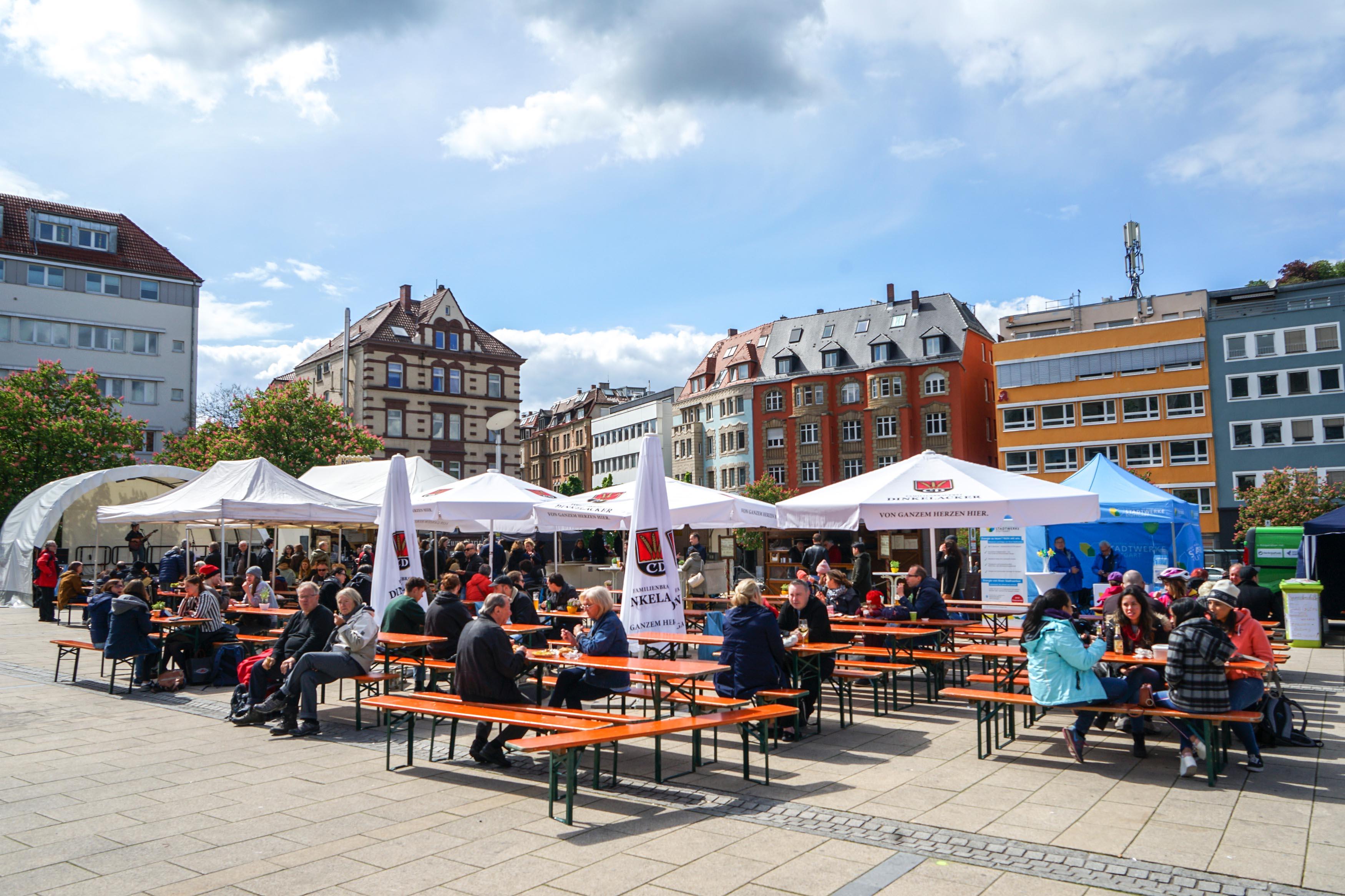 Blick über den Platz mit Gästen an Bierbänken