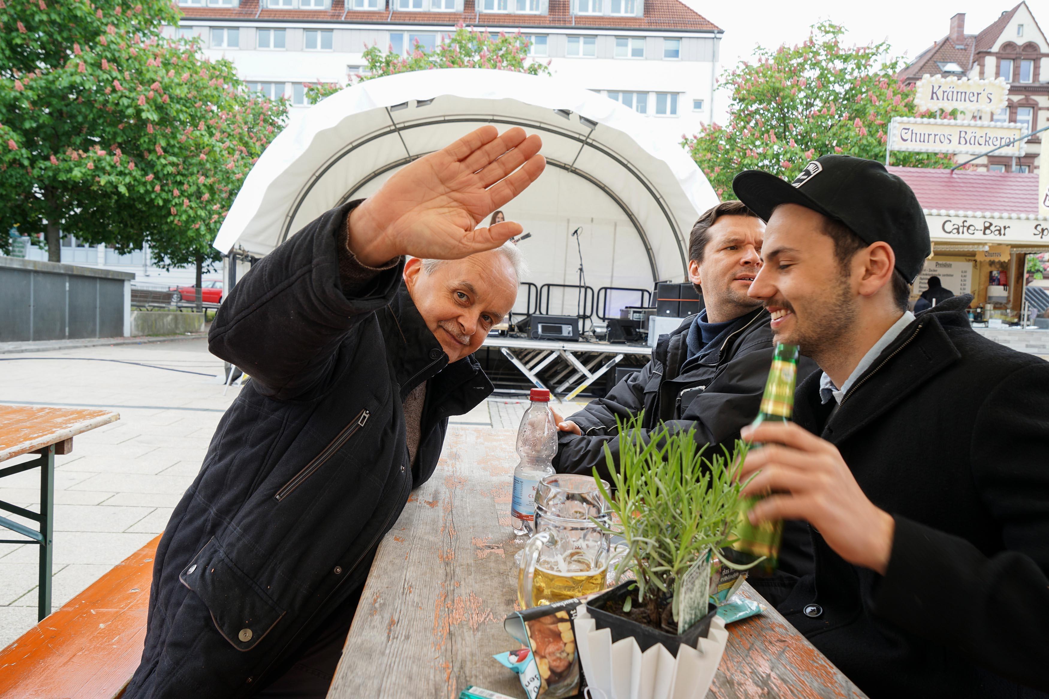 3 Männer sitzen an Bierbank, einer winkt in die Kamera