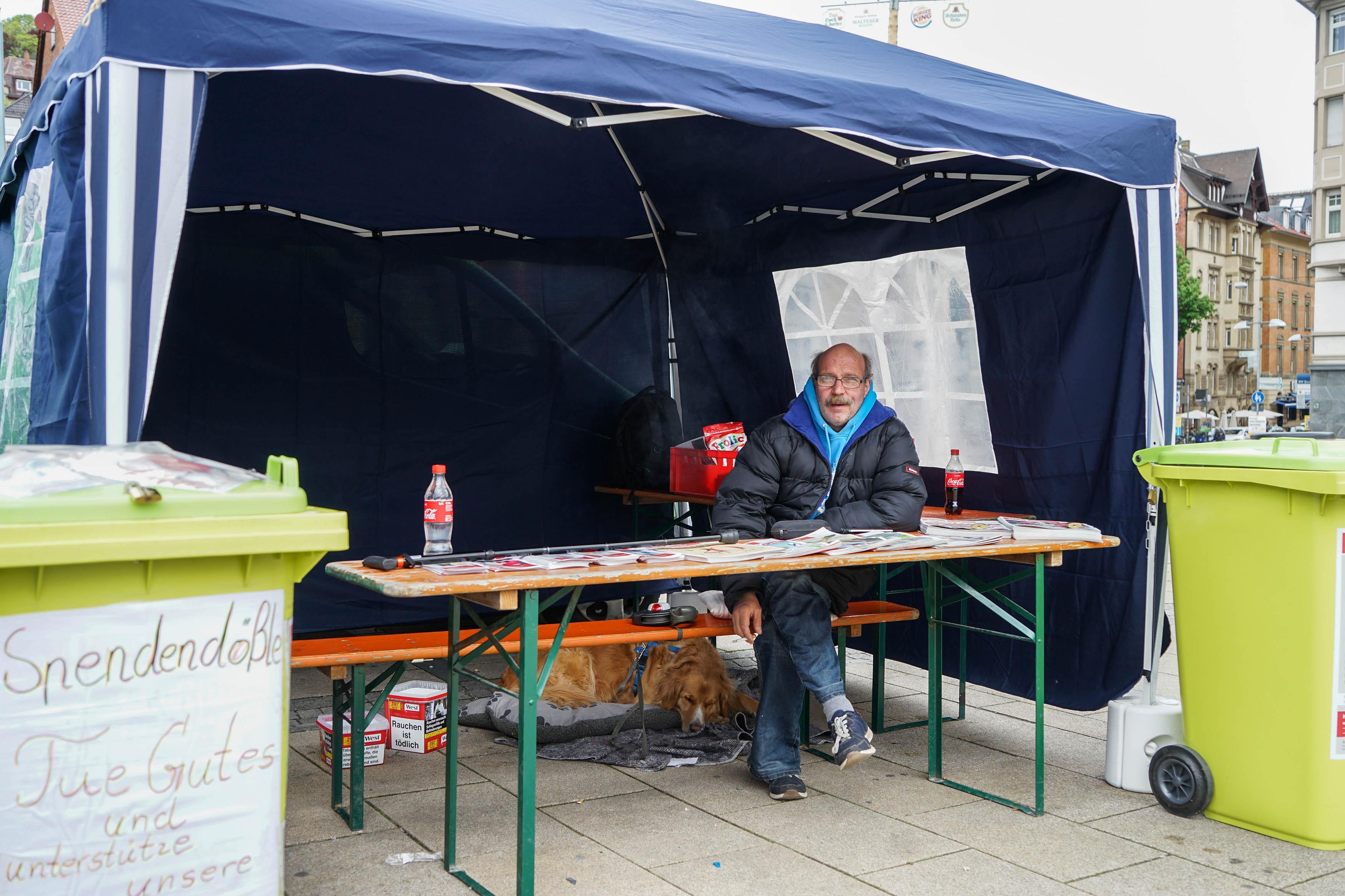 Mann mit dick gepolsteter blauem Anorak sitzt im offenen Zelt vor einer Bierbank