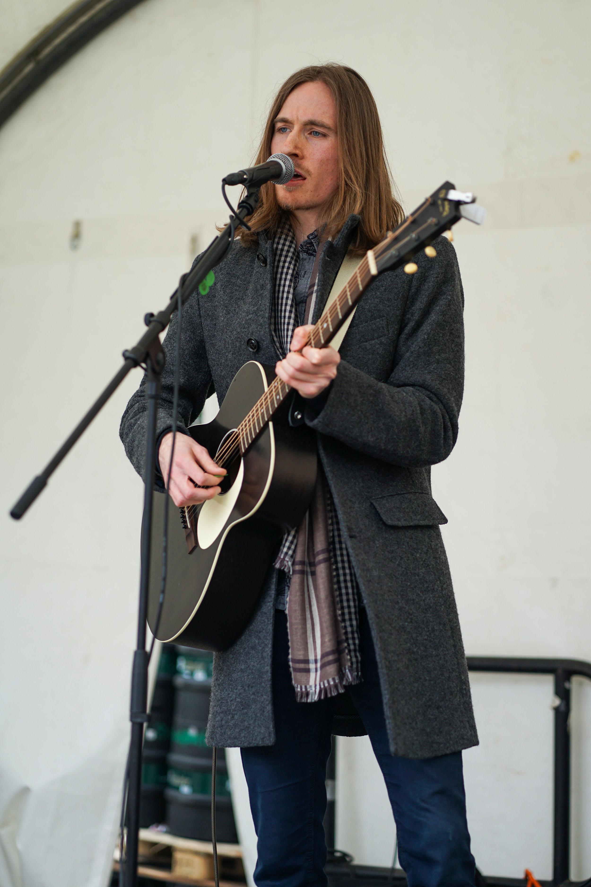 Mann schulterlangen hellbrauen Haaren, grauem Mantel und Gitarre