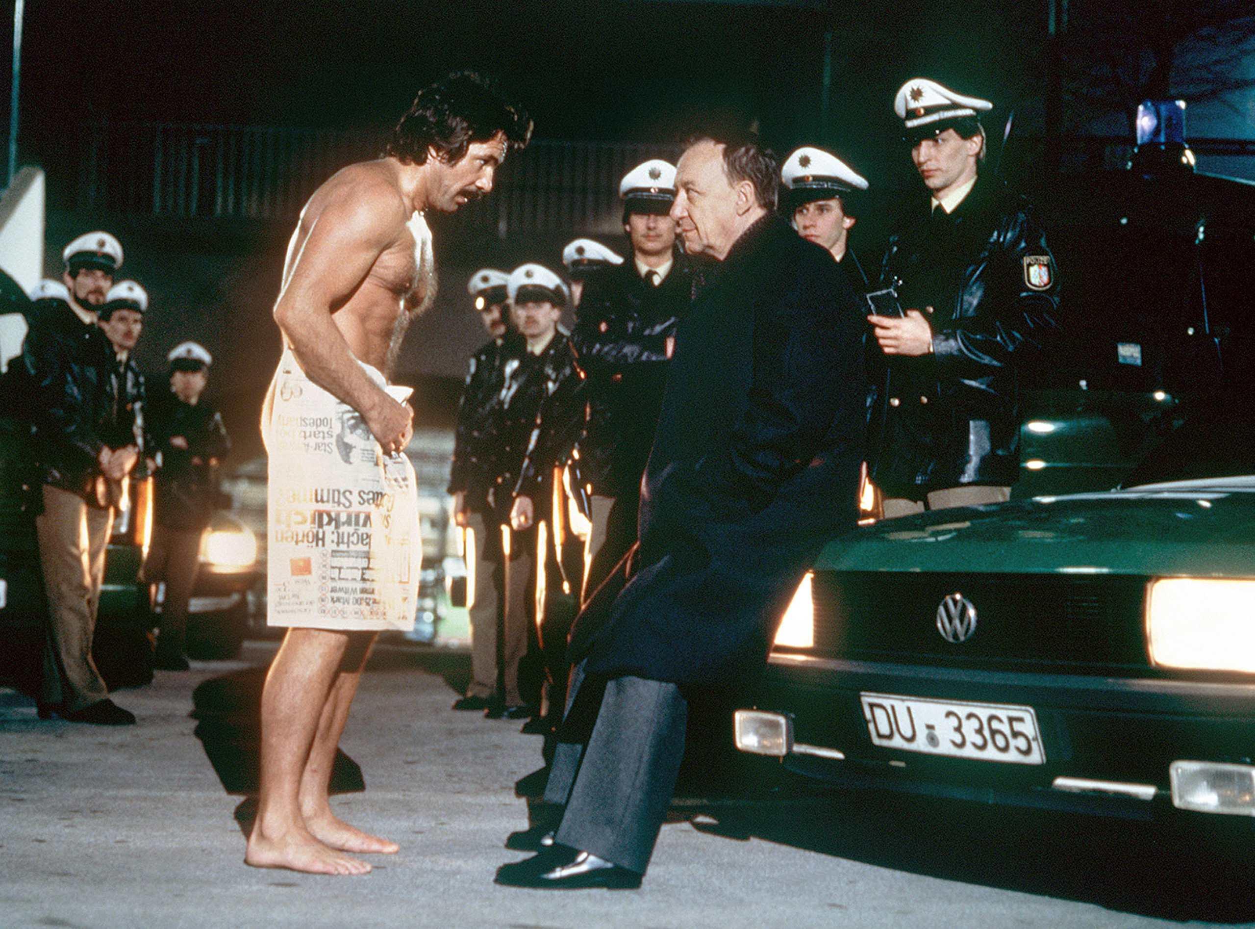"""""""Tatort""""-Kommissar Horst Schimanski, gespielt von Götz George, steht nur mit einem Handtuch bekleidet vor seinen teilweise amüsierten Kollegen"""