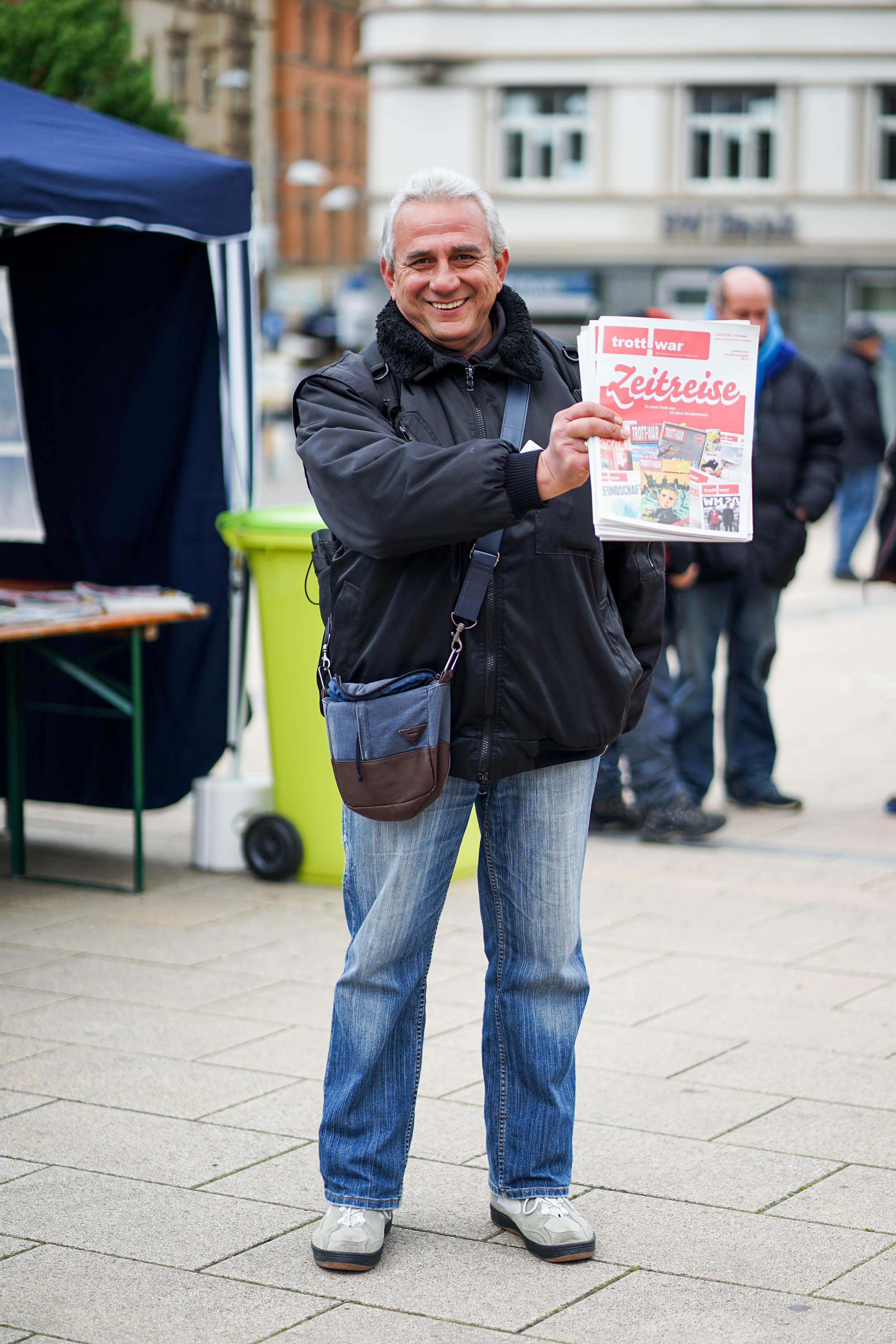 grauhaariger Verkäufer mit dunkelblauer Jacke hält Trott-war hoch und lacht