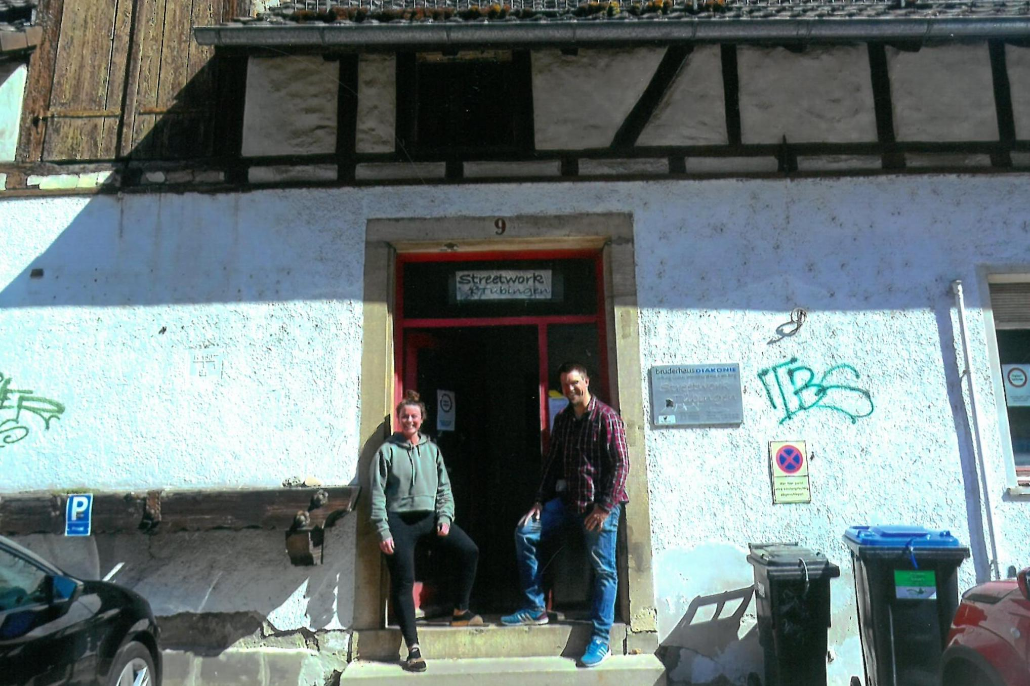 Morwenn Heimerdinger und Felix Seeger lächelnd vor dem Eingang des Streetwork Tübingen