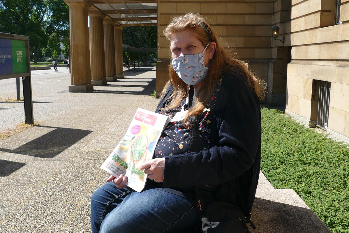 Frau mit langen rotbrauen Haaren und Mundschutz sitzt vor der Oper
