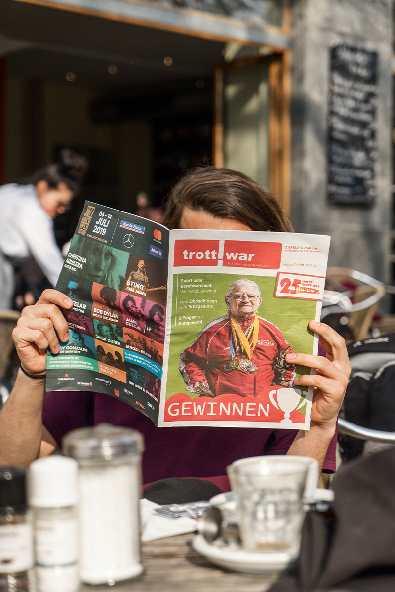 ein Mensch liest - versteckt hinter der aufgeschlagenen Zeitung - Trott-war