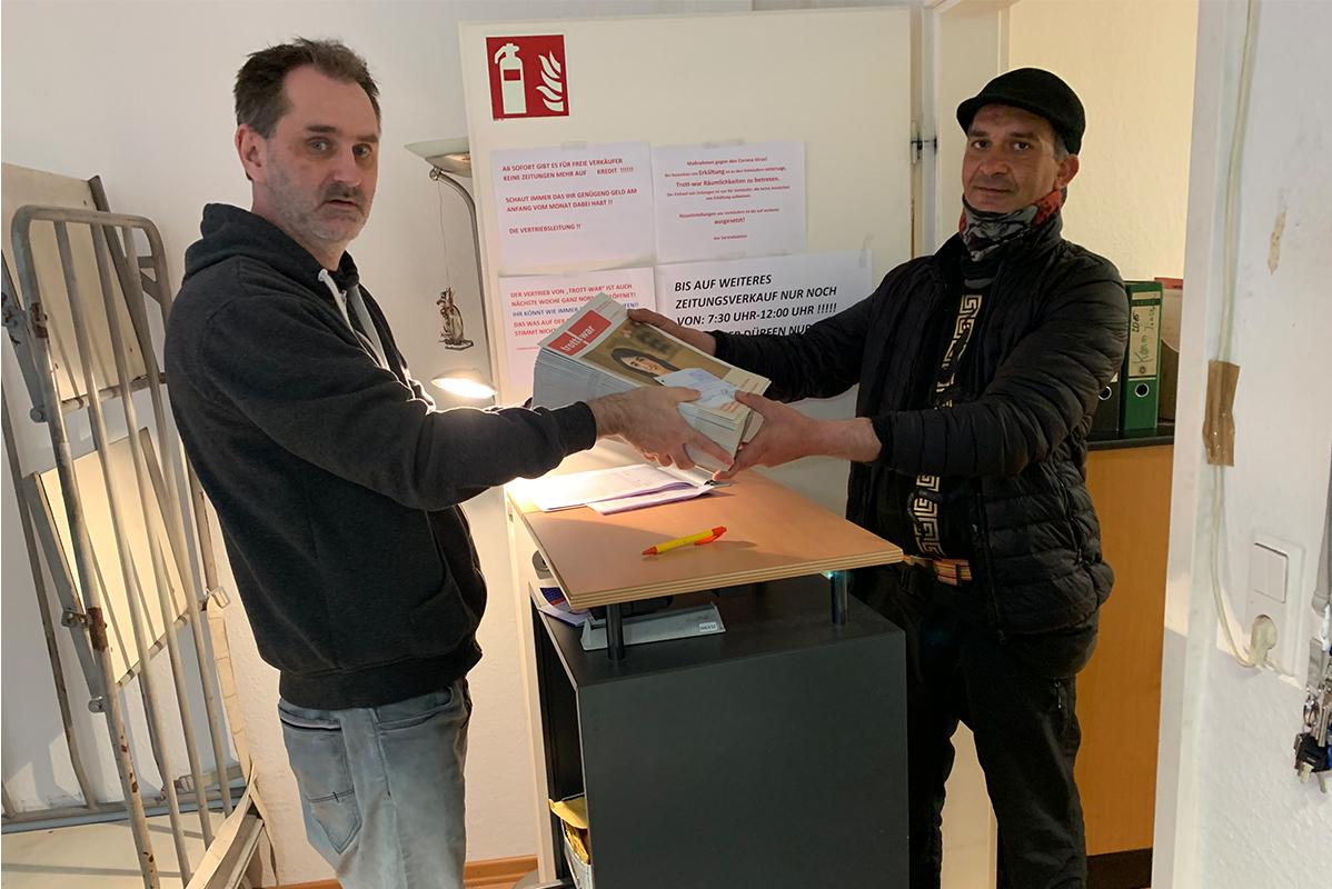 Marcus reicht einem Verkäufer Zeitungen