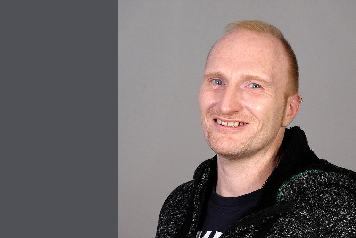 lächelnder Mann mit mittelbraunen Haaren und mittleren Alters in schwarzem Hoodie