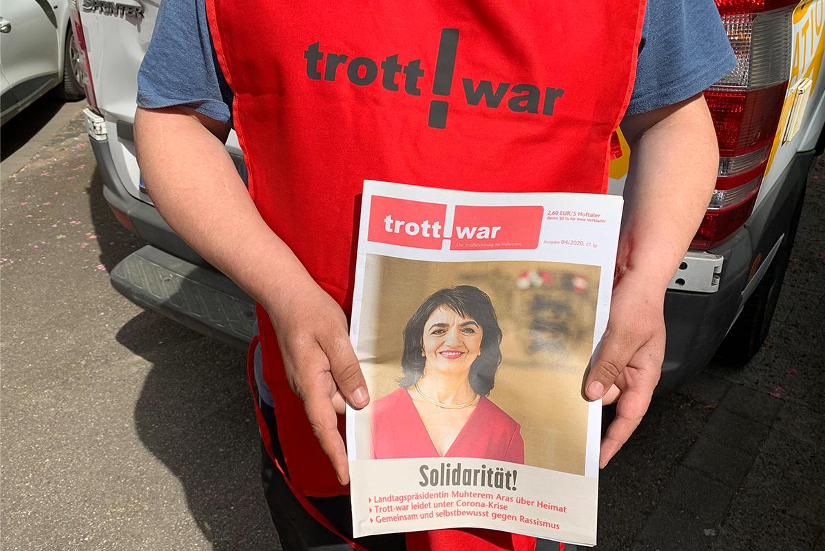 Hände von Trott-war-Verkäufer in rotem Kittel, die Heft halten
