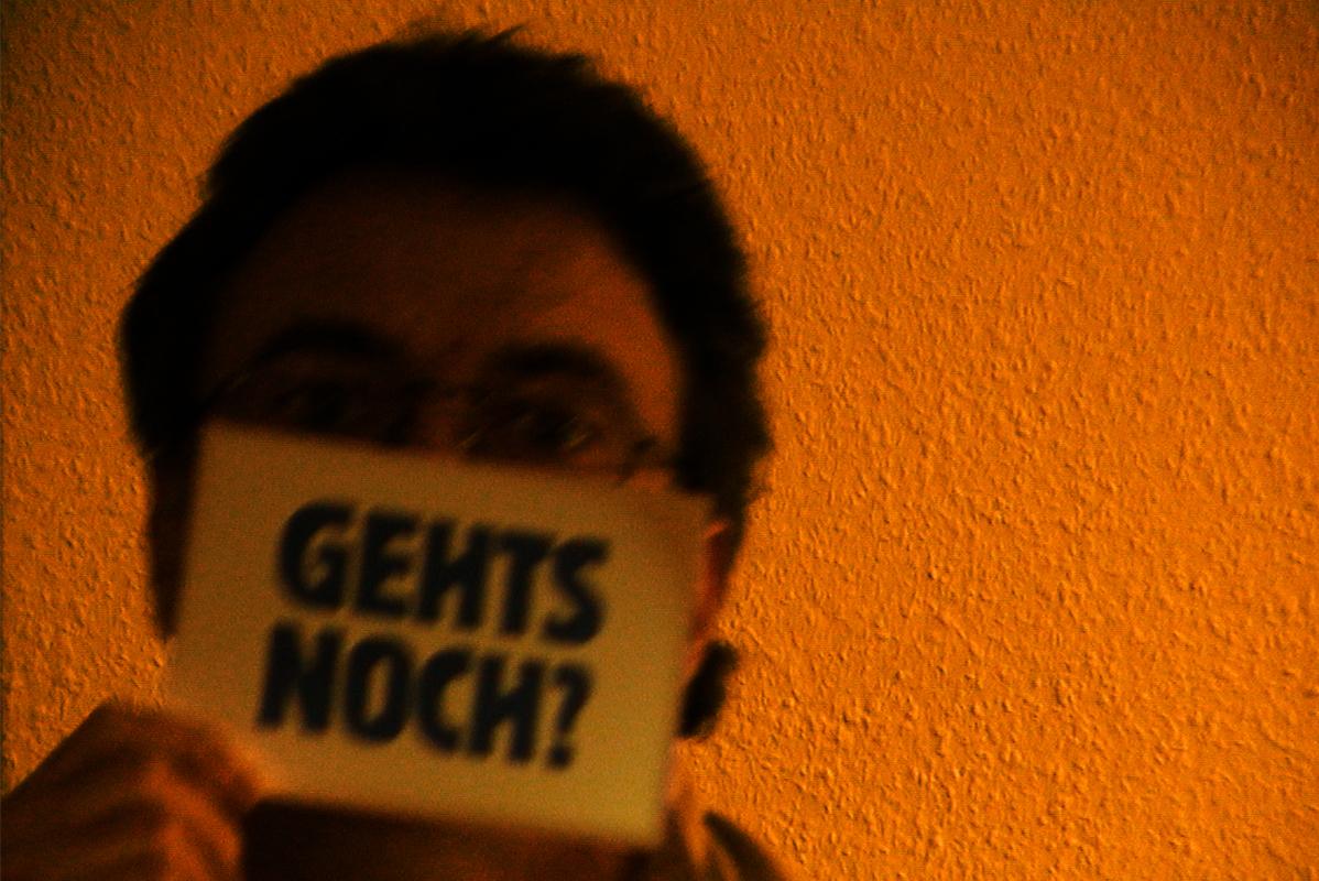 """dunkelhaariger Mann hält Schild """"Gehts noch?"""" vor Mund und Nase"""