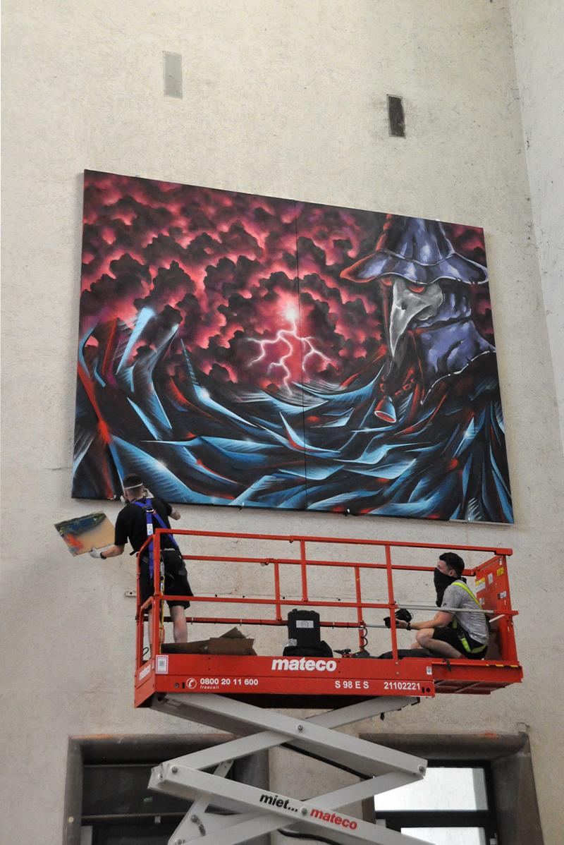 2 Sprayer bearbeiten ein Graffiti auf einer Hebebühne