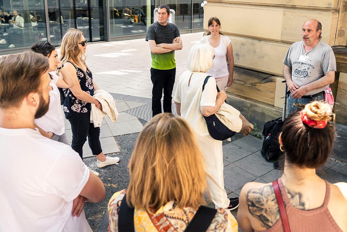 Gruppe steht im Kreis um Stadtführer herum
