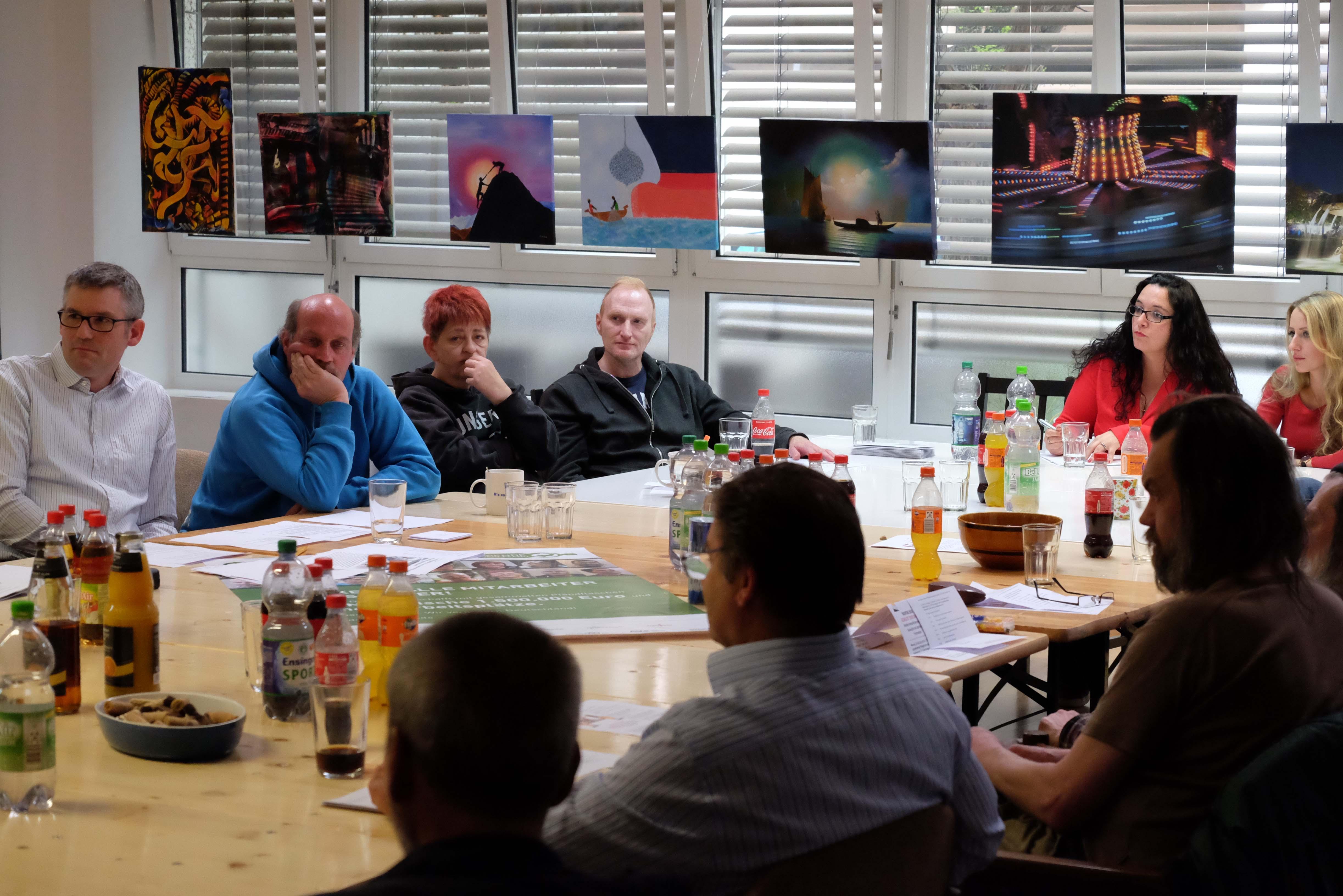 Menschen sitzen in der Trott-war-Galerie um einen Tisch