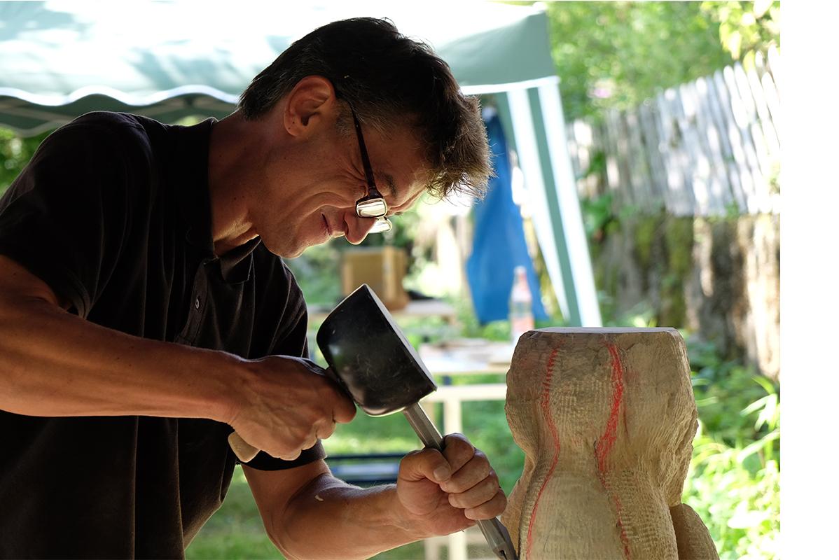 kurzhaariger Mann behaut Steinblock mit Werkzeug