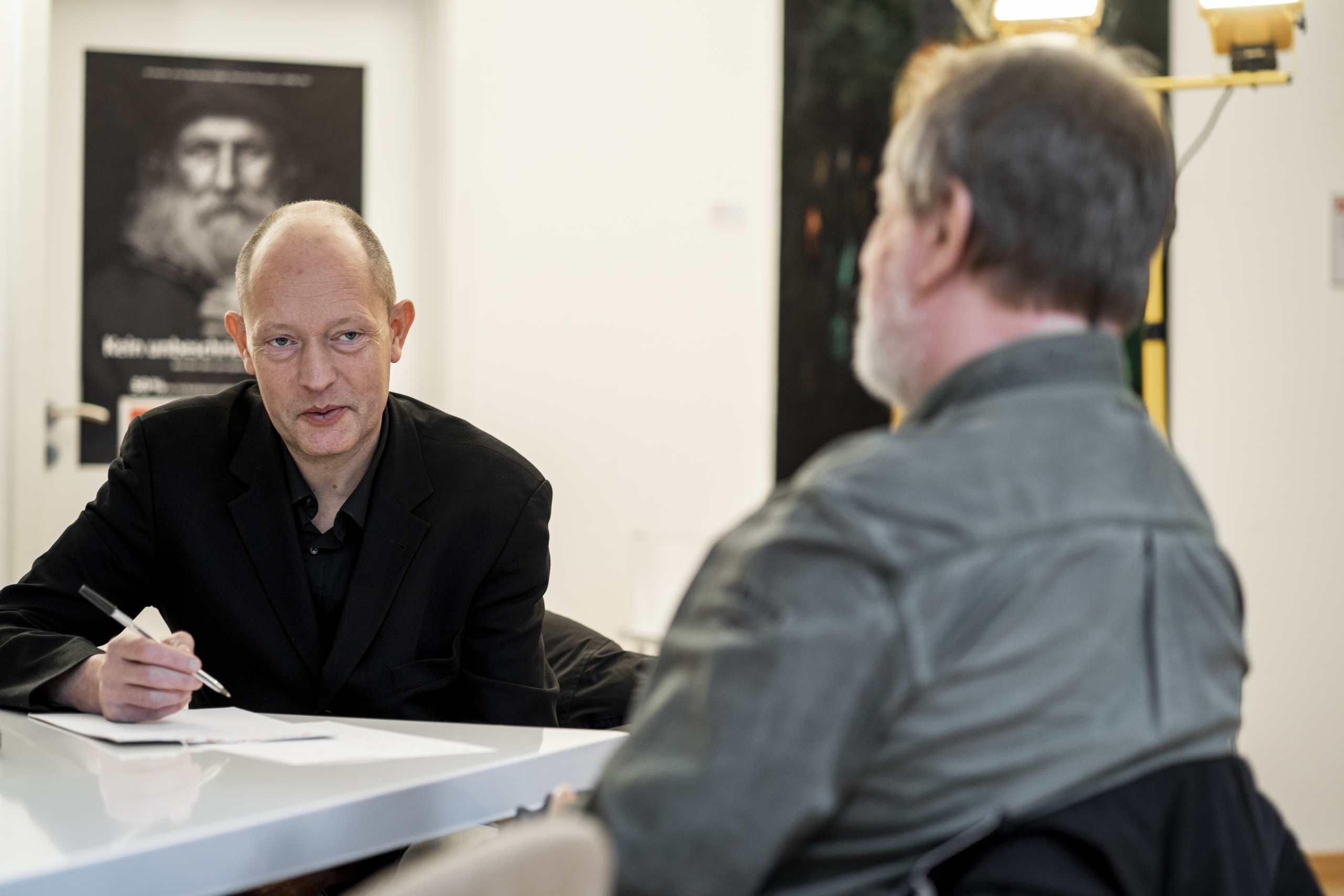 Journalist Frank Schön interviewt Trott-war-Geschäftsführer Helmut Schmid und macht Notizen