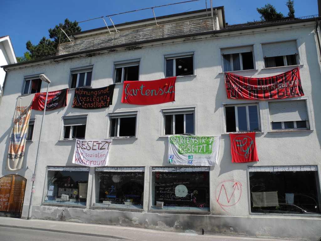 Das besetzte Haus Gartenstraße 7 in Tübingen mit Bannern mit Forderungen und Parolen, die aus dem Fenster hängen
