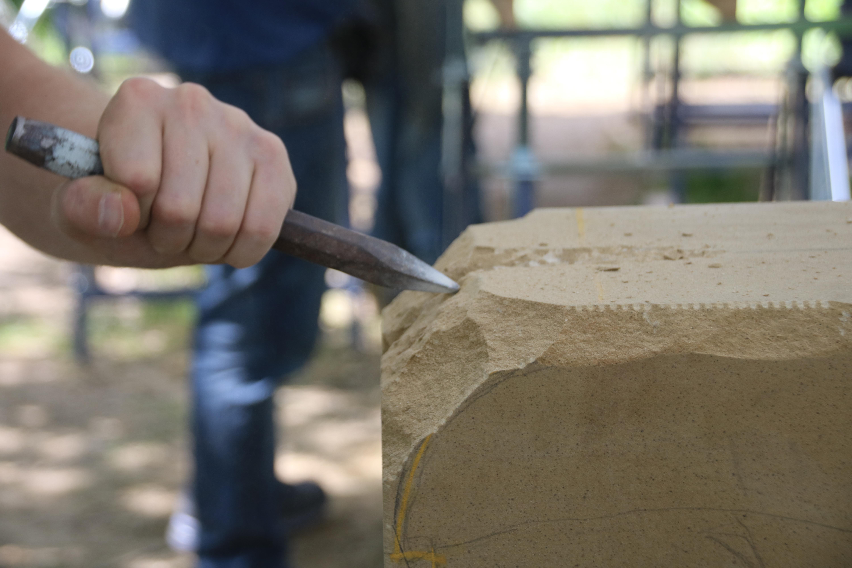 Eisen, angesetzt an einen Sandsteinquader mit Bearbeitungsspuren der vorherigen Arbeitsgänge