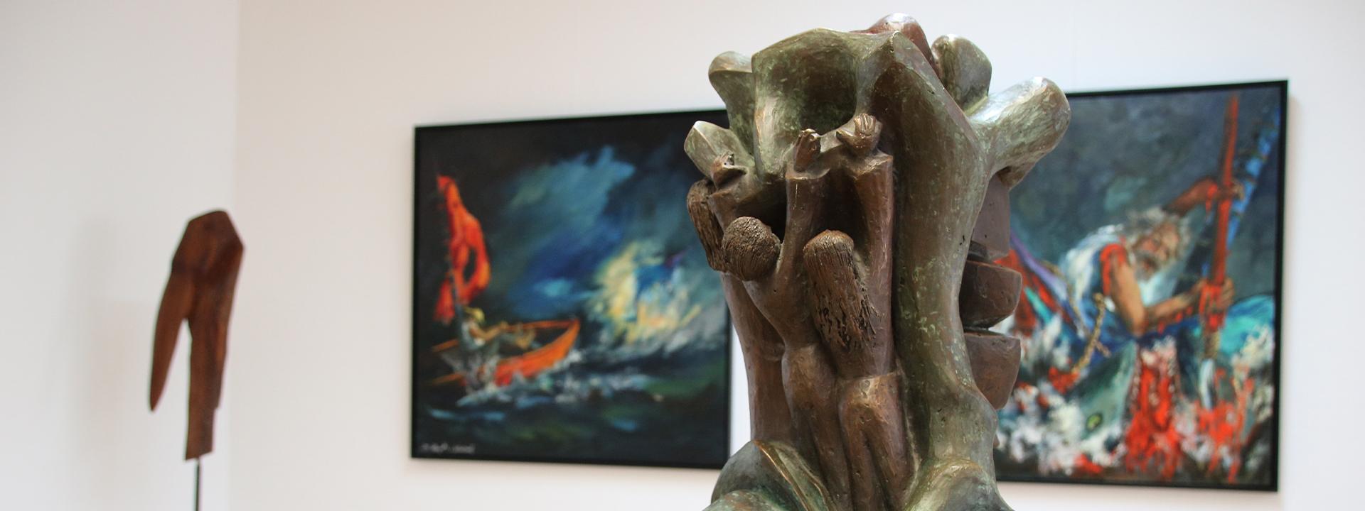 Eine kleine Bronzeskulptur im Vordergrund steht vor großformatigen Ölbildern