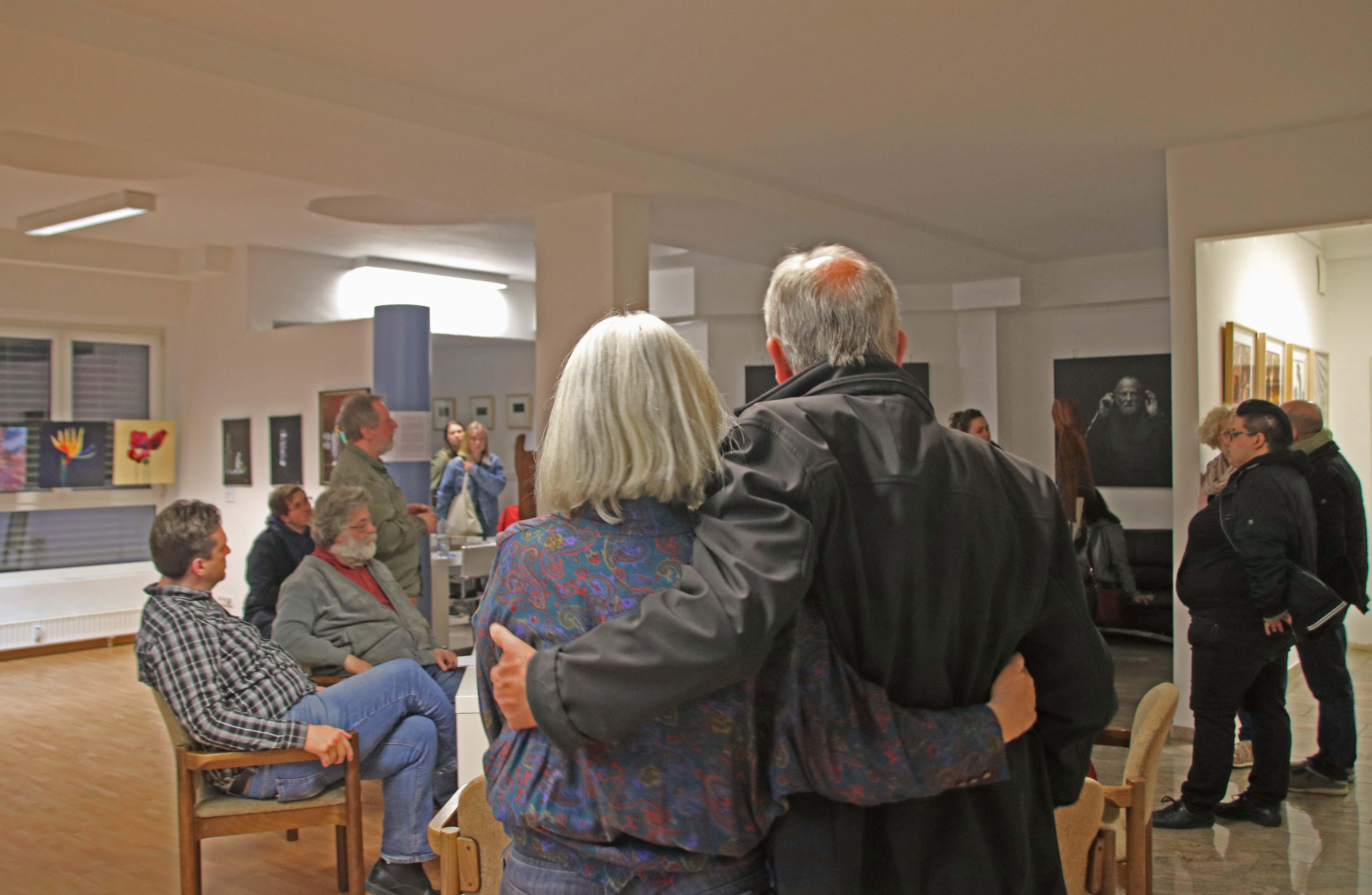 2 Zuhörende Arm in Arm von hinten