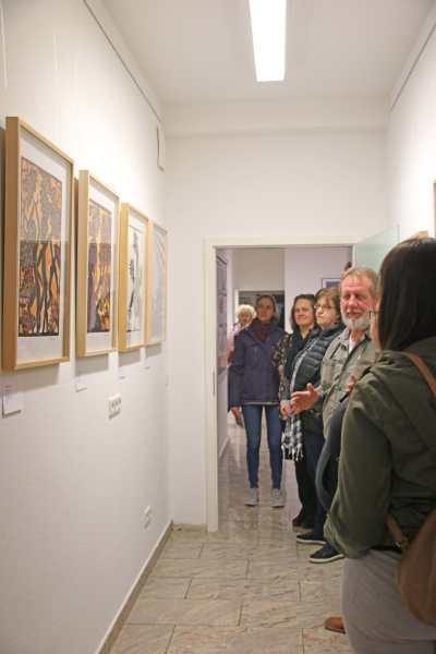Galeriebesuchende und Galerieführer stehen vor Bildern
