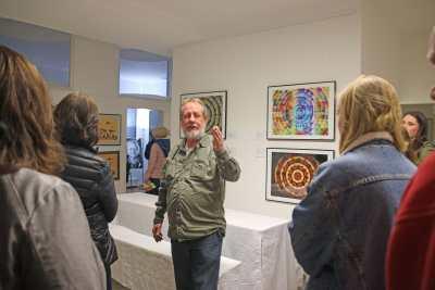 Schmid steht in Galerie und weist auf ein Bild