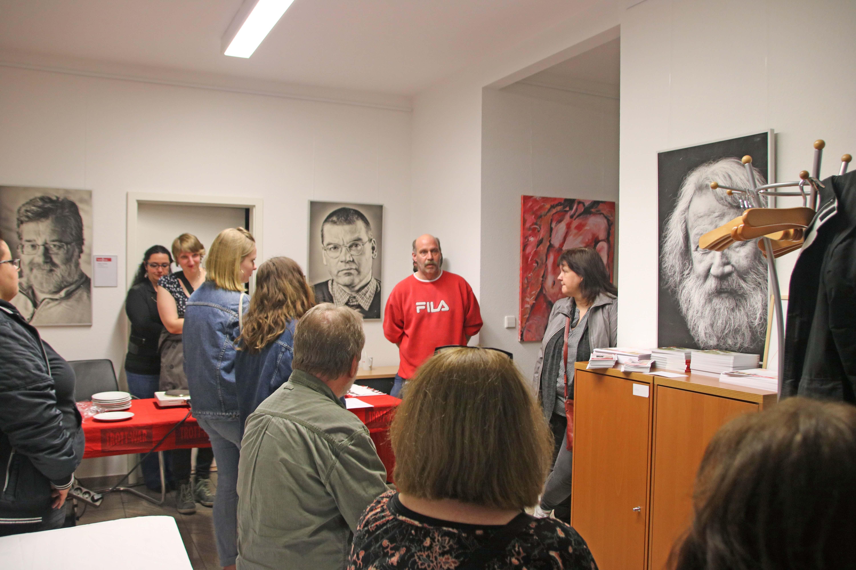 Mann mit rotem Pulli steht vor Zuhörenden