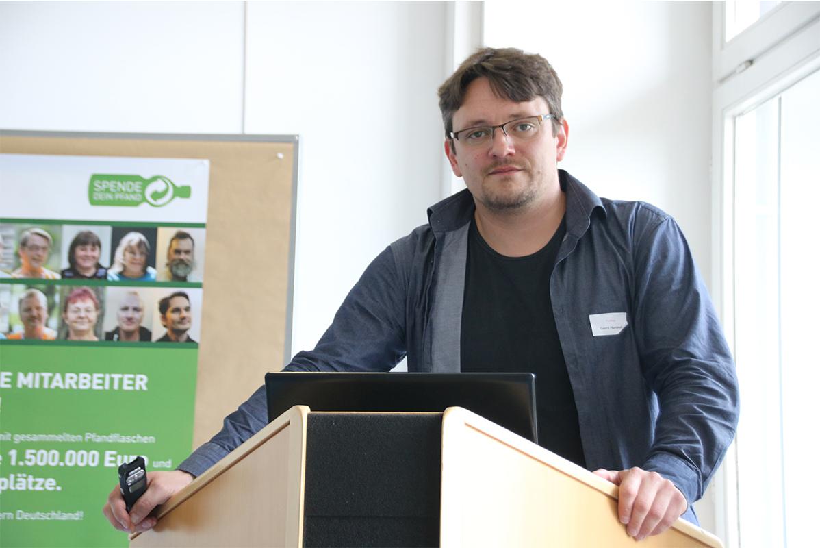 junger Redner mit mittelbraunem Haar und Brille an Rednerpult