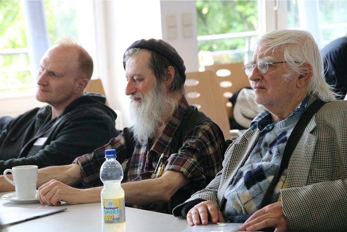 3 männliche Tagungsgäste an ihrem Tisch