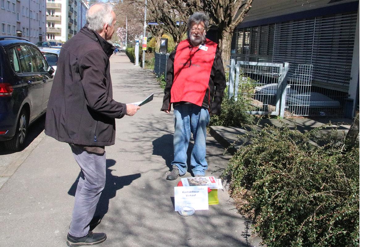 ein Mann hat Geld in Glasschüssel gelegt und eine Straßenzeitung von einem Stapel vor dem Verkäufer genommen.