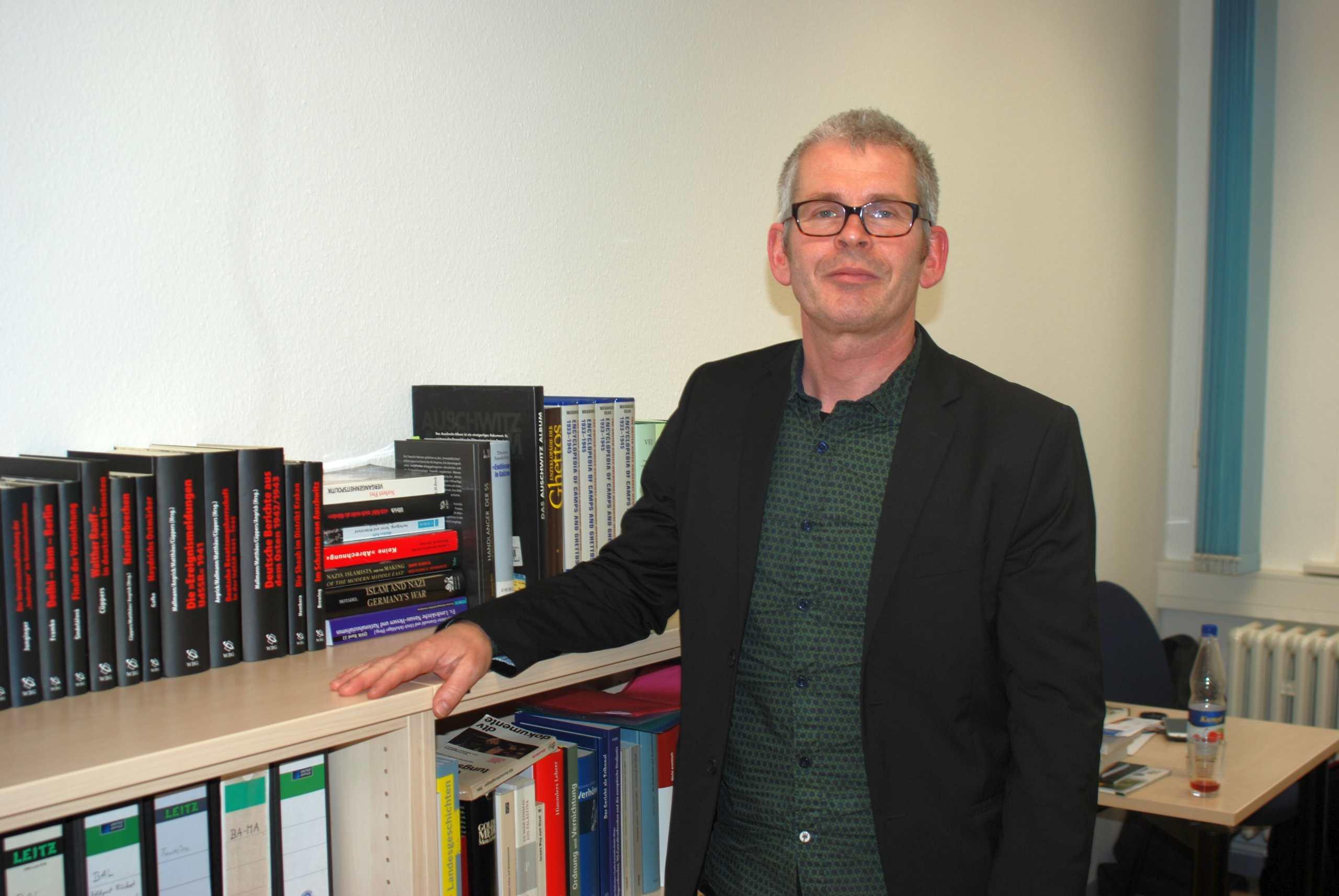 Martin Cüppers vor einem Bücherregal mit einschlägigen Werken über NS-Verbrechen