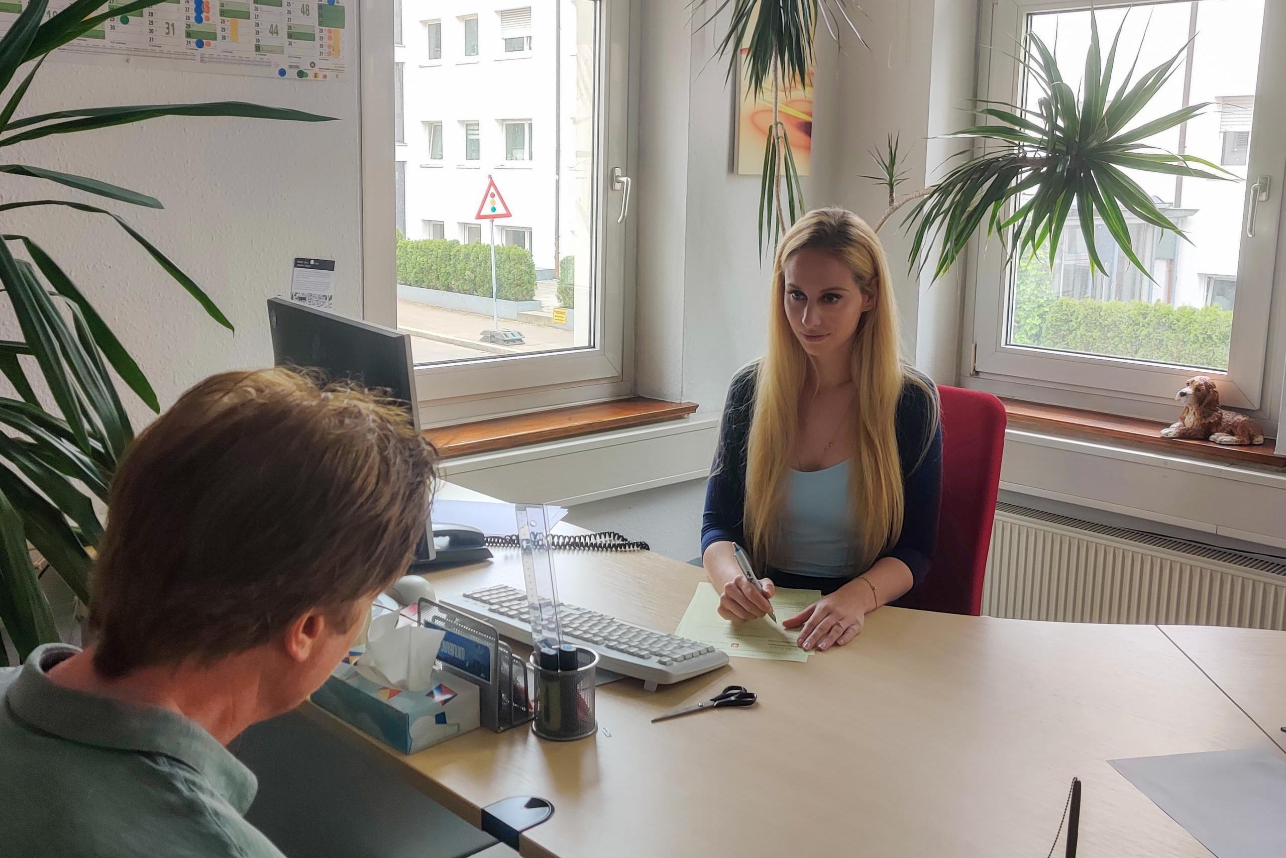 Sozialarbeiterin hinter Schreibtisch, im Bildvordergrund Person, die sich beraten lässt