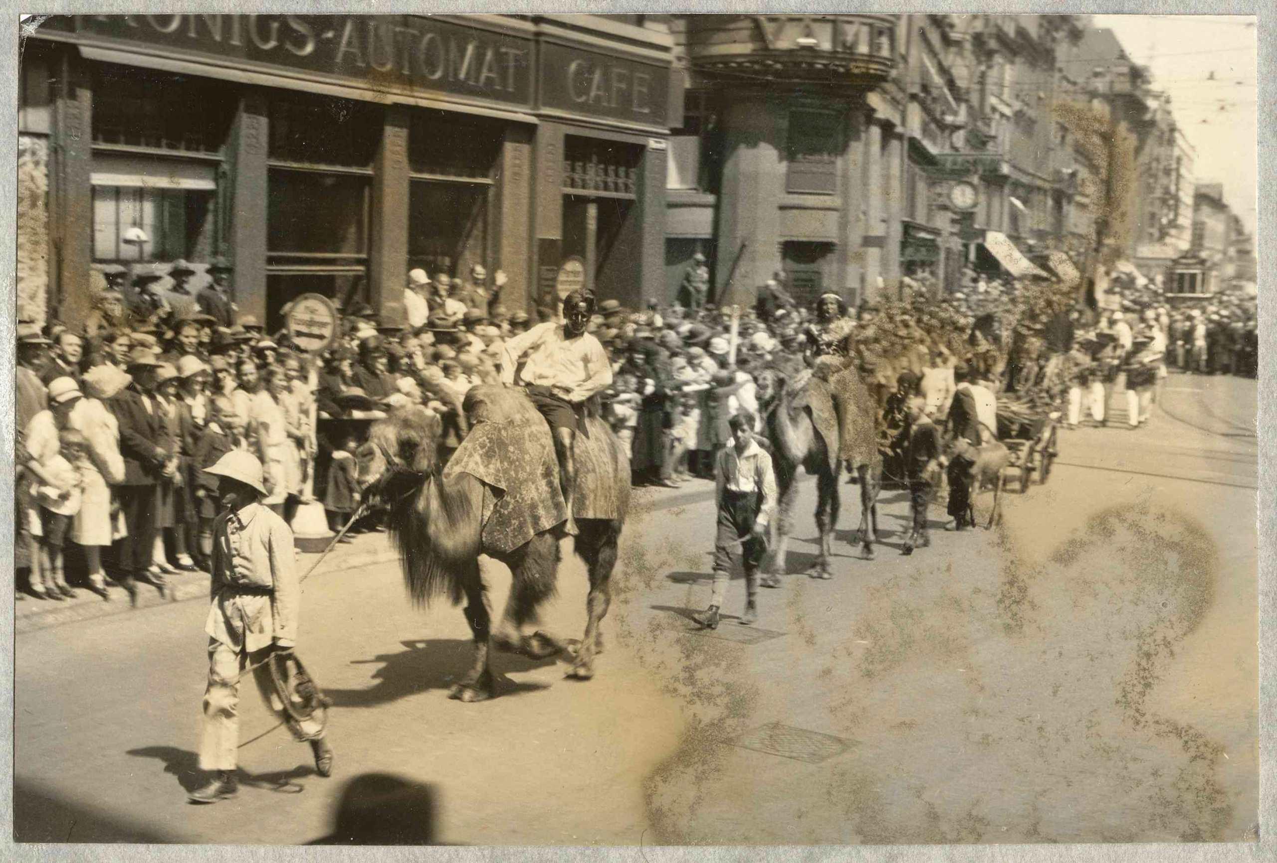 Schwarz angemalte Weiße werden während der Kolonialtagung 1928 in Stuttgart auf Kamelen durch die Straßen Stuttgart geführt