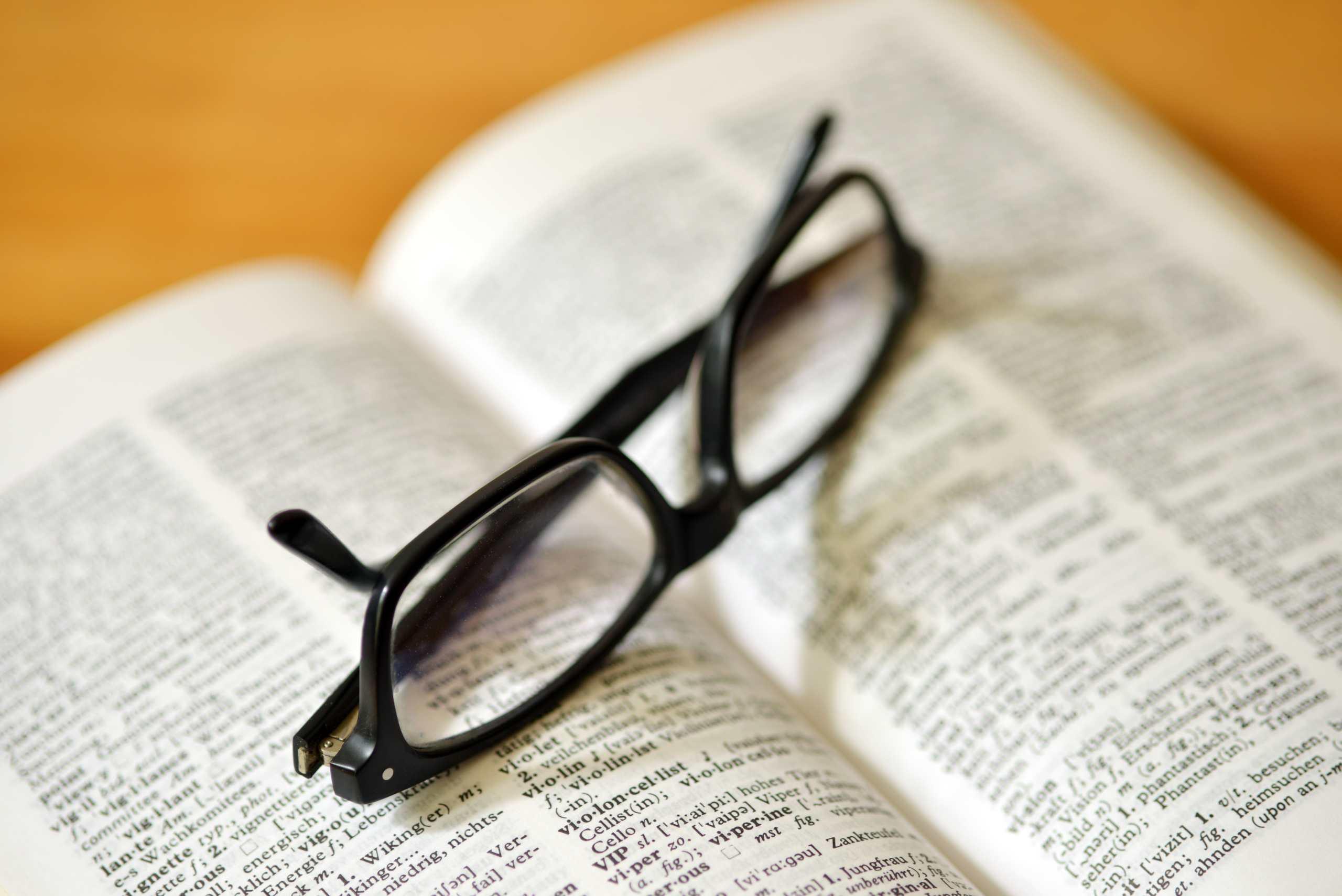 Lesebrille, zusammengeklappt abgelegt auf einem aufgeschlagenen Wörterbuch