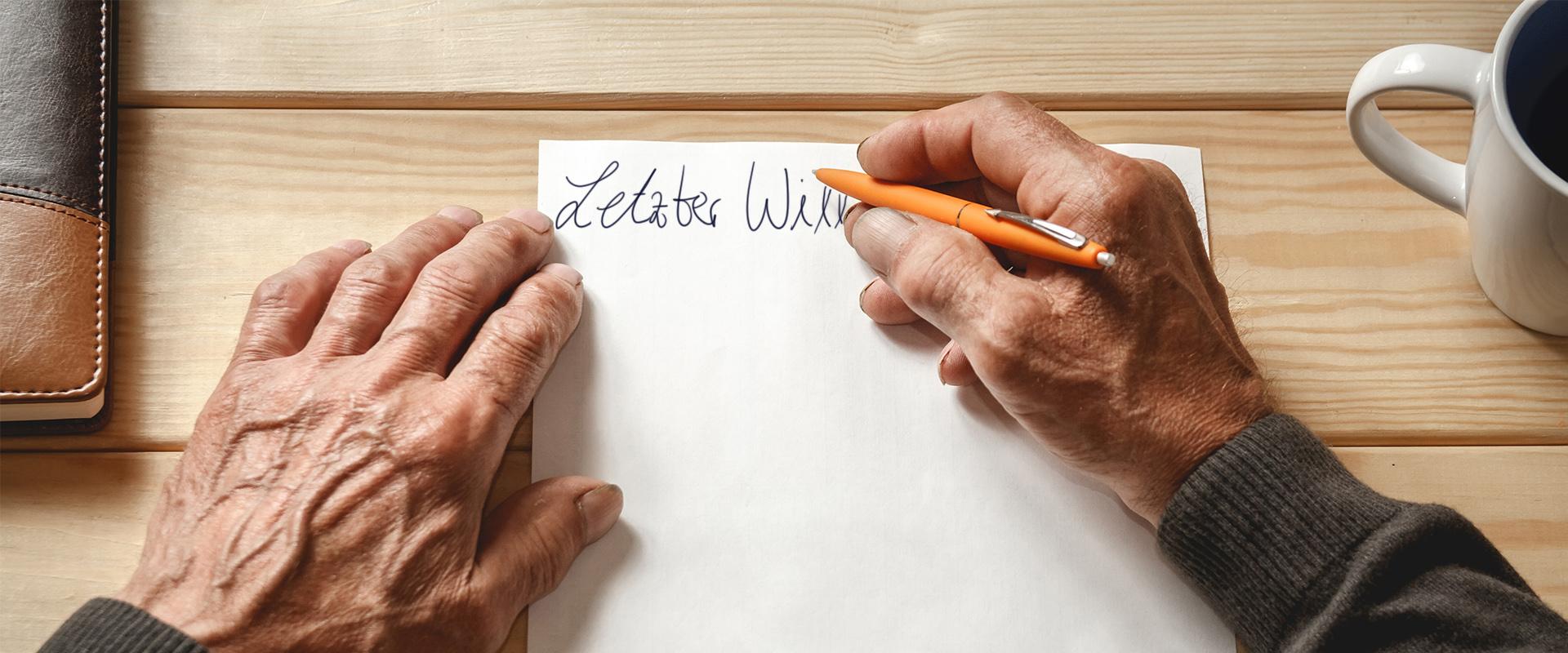 """Alte Hand schreibt auf Papier """"Letzter Wille"""""""