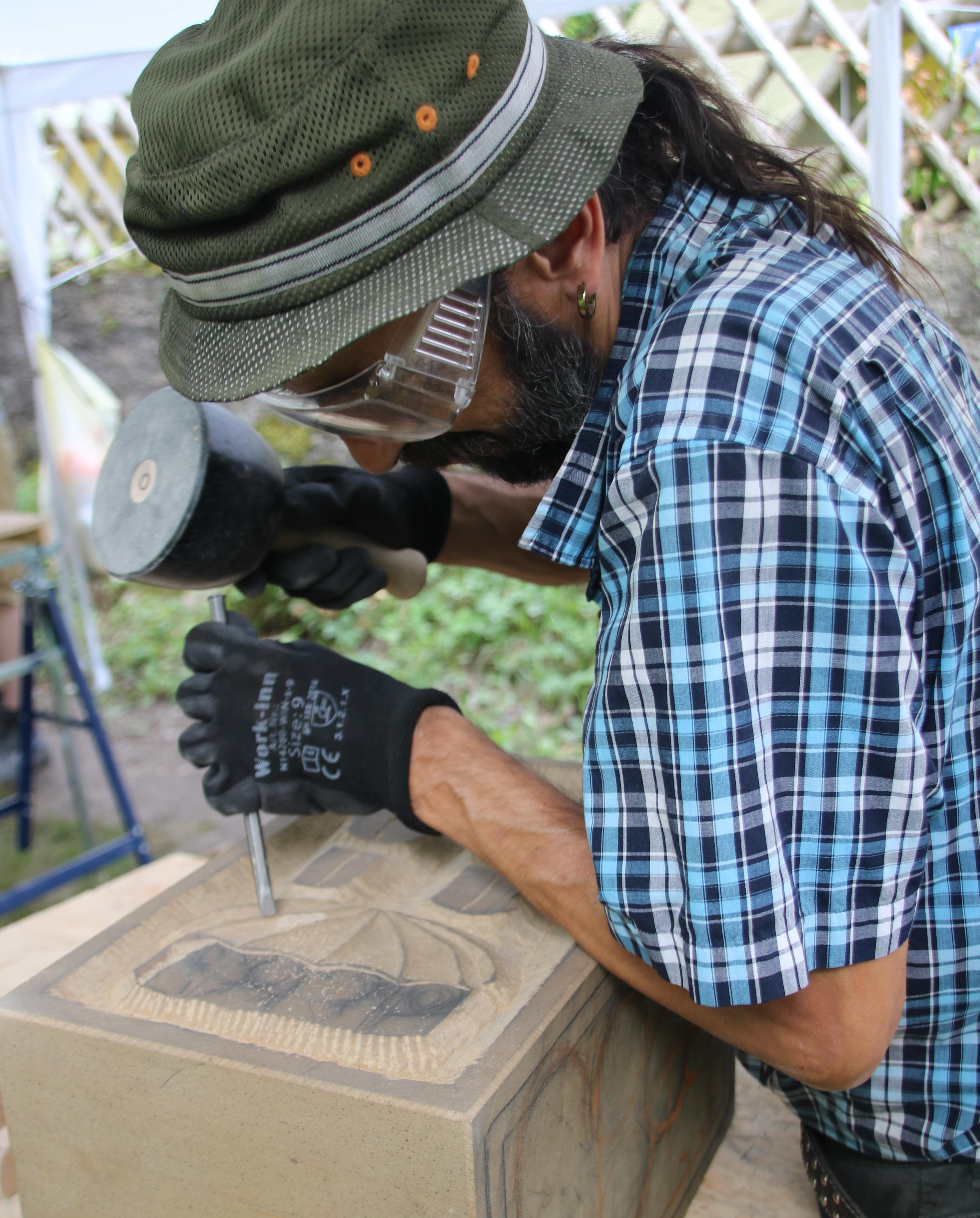 Künstler Marius arbeitet mit schmalem Eisen Feinheiten aus