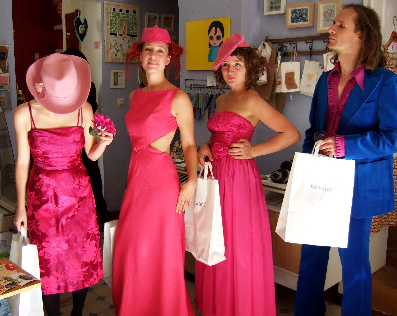 Frauen führen rote Kleider vor