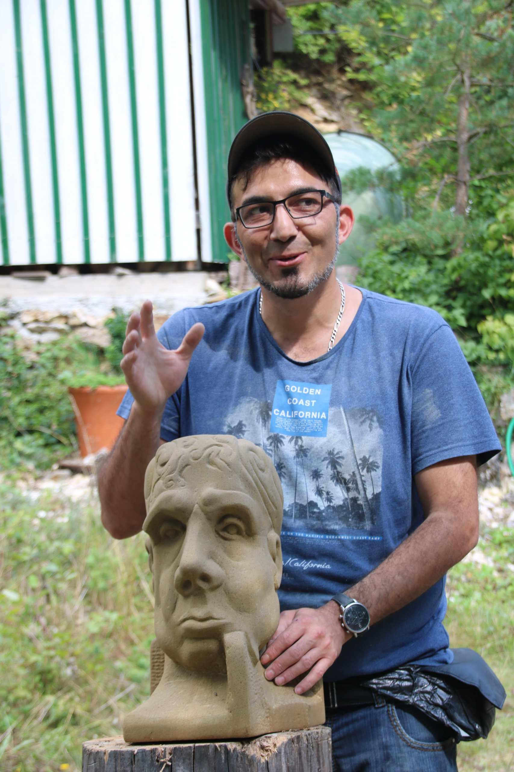 Künstler Murat gestikuliert über seinem Werk, der Büste
