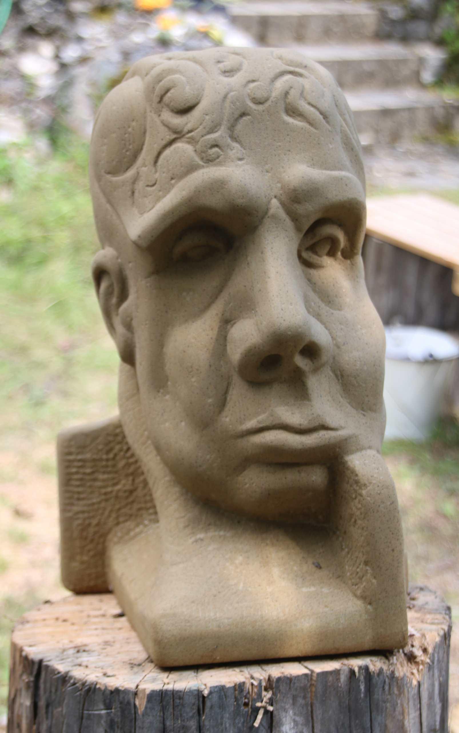 eine Büste aus Sandstein, die einen nachdenklichen oder traurigen Menschen zeigt