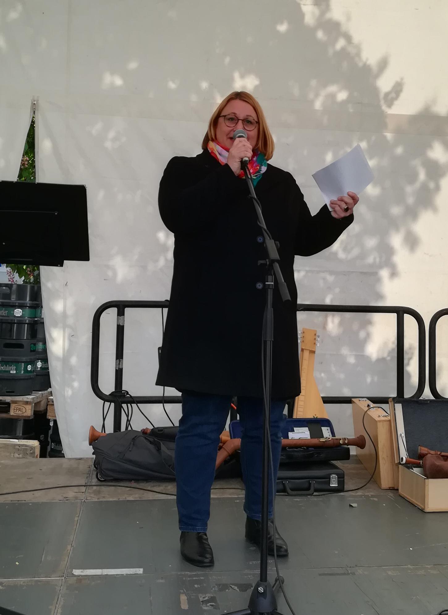 Blonde Frau mit Brille und Mantel am Mikrofon