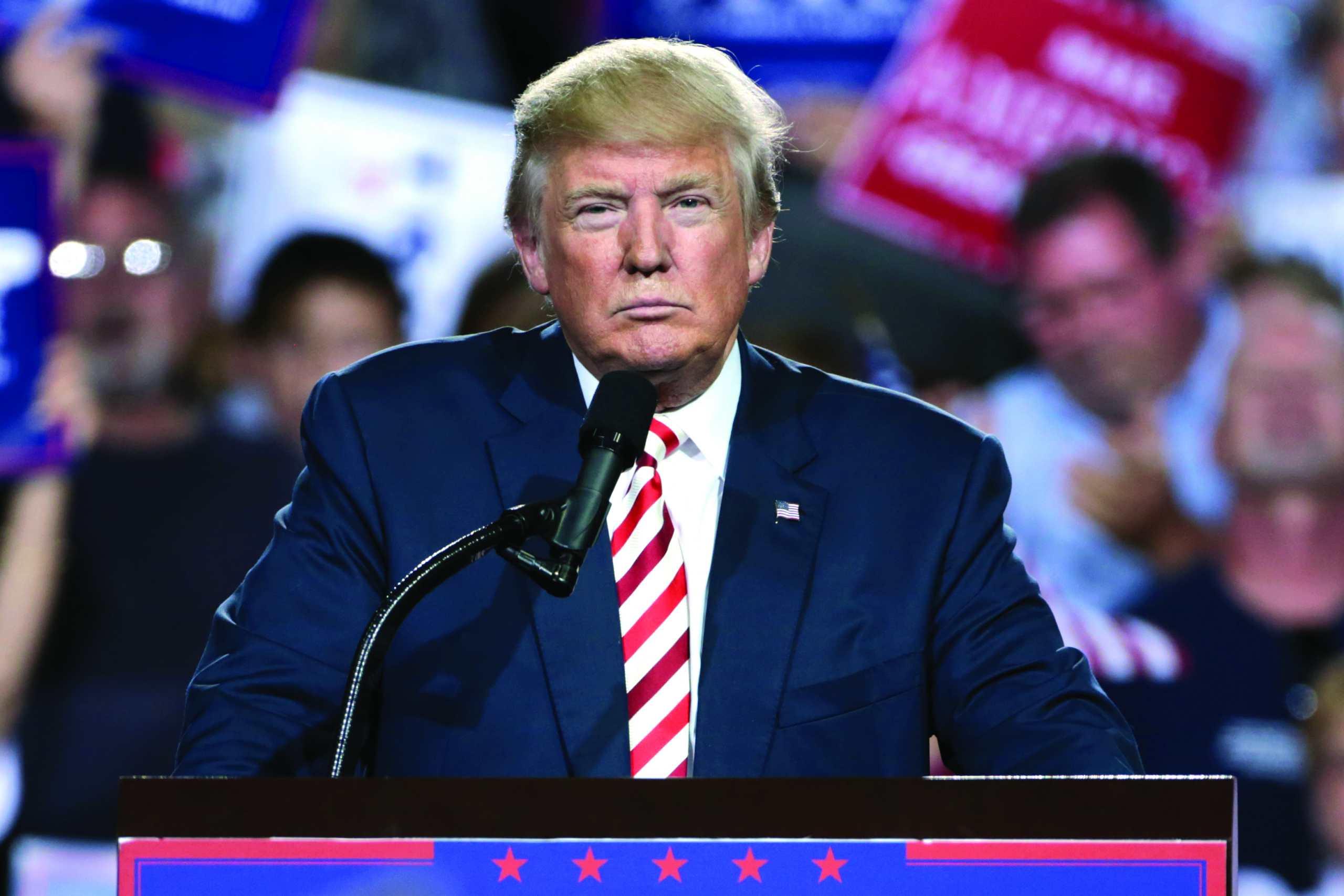 Donald Trump mit finsterer Miene vor einem Mikrofon