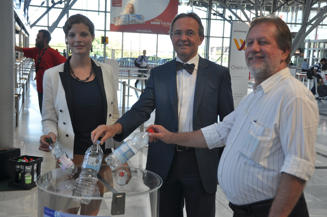 Eröffnung des Projekts - Antonia Schmück von Enactus, der ehemalige Flughafengeschäftsführer Prof. Georg Fundel und Trott-war-Geschäftsführer Helmut Schmid werfen Pfandflaschen in Sammelcontainer