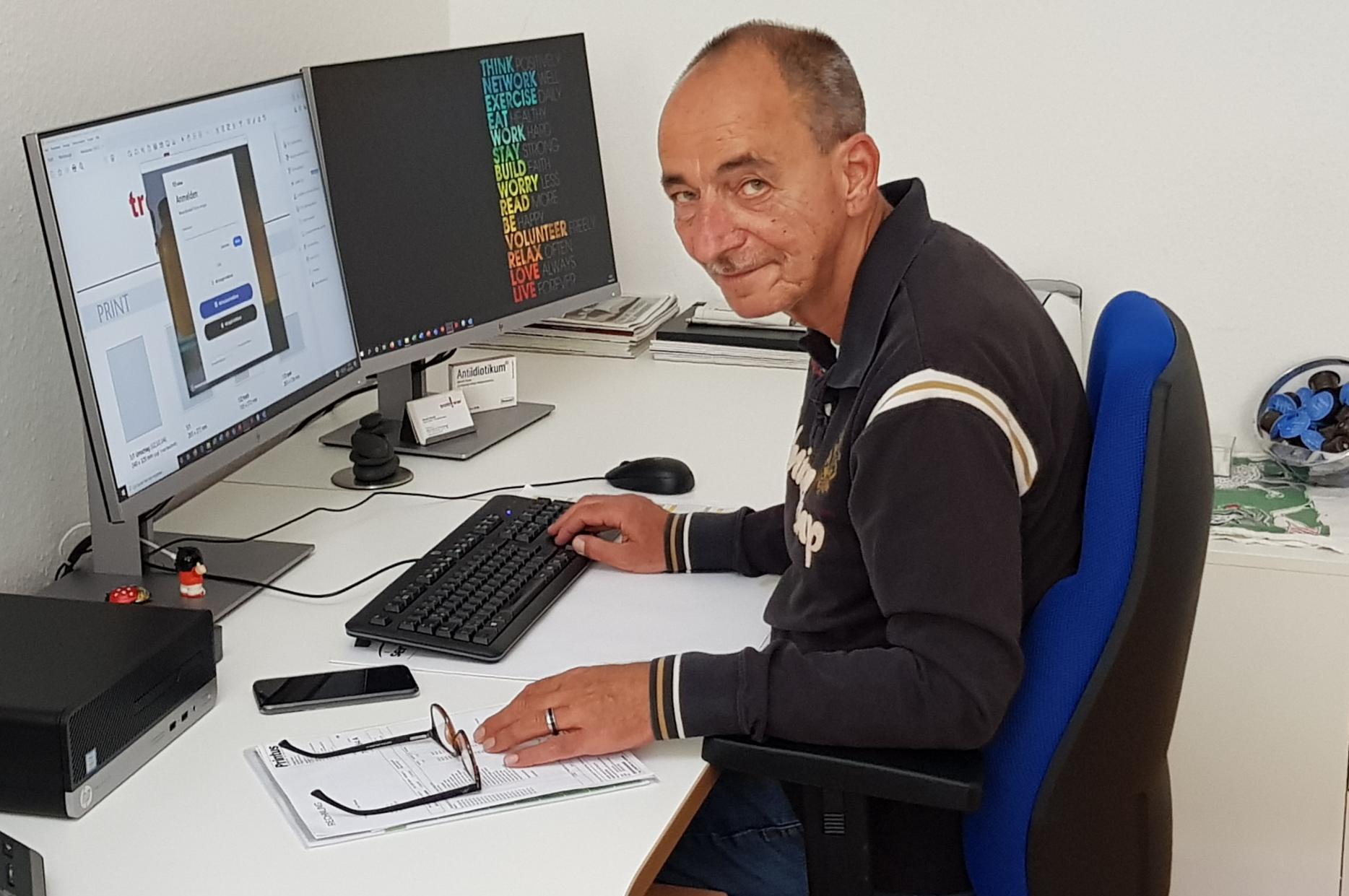 Bernd Gebauer vor seinem PC mit zwei Bildschirmen