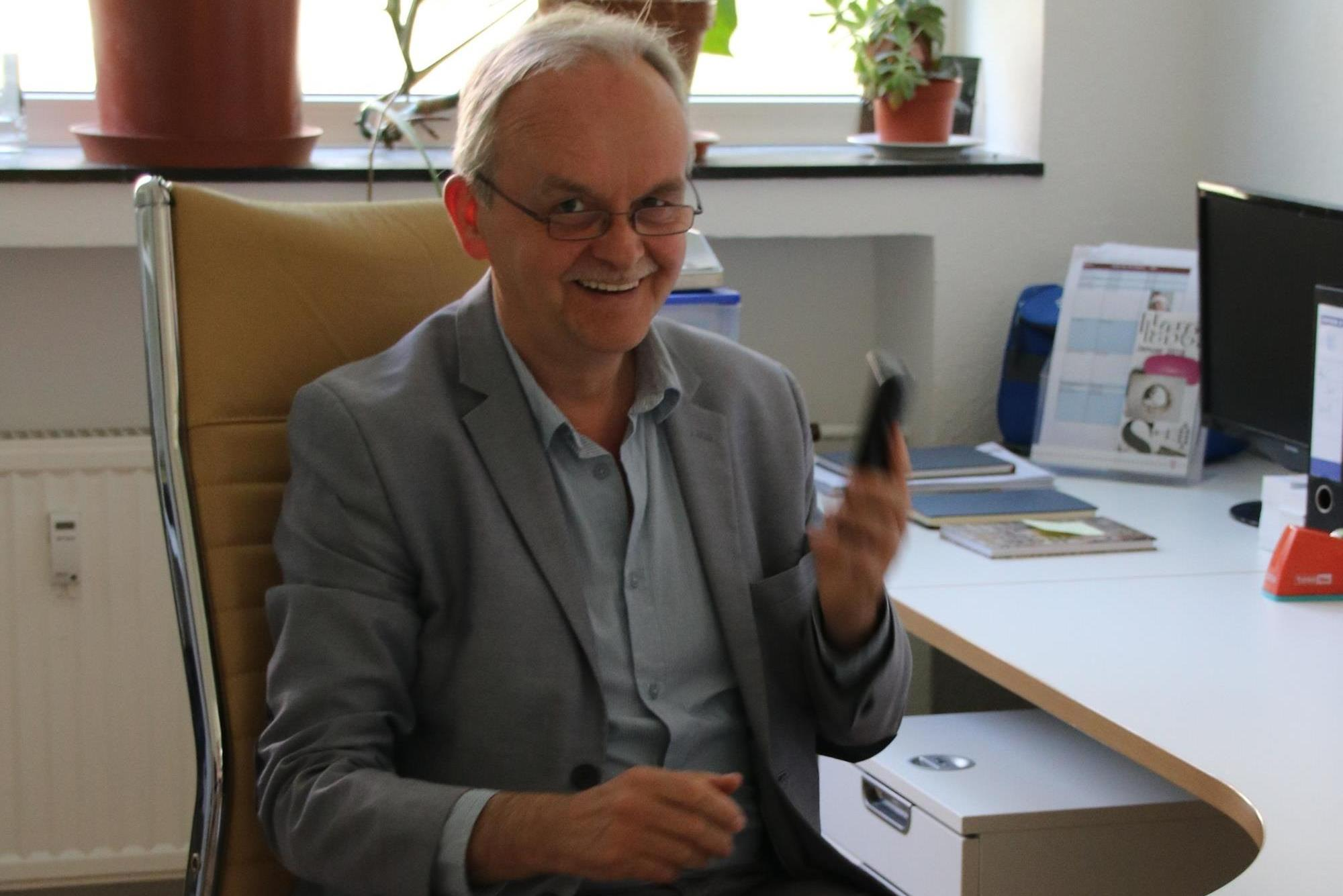 Vertriebschef Uwe Determann lachend mit Telefon in der Hand